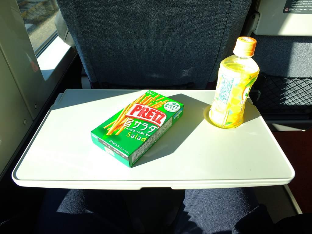 E235系1000番台 グリーン車座席テーブル(広げた状態でお菓子をおいた)